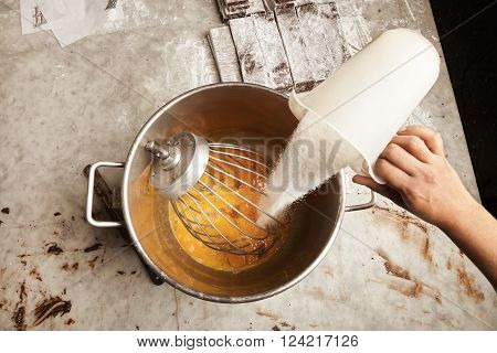 Professional Cooking Process. Black Man Chief Pours Measure Cup Of Sugar In Big Steel Industrial Buc