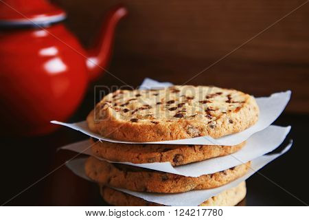 Close view of focused tasty homemade crunchy cookies with chocolate bites in front of unfocused vintage red teapot with hot beverage breakfast meal