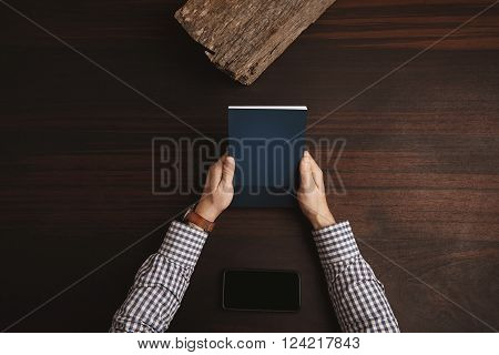 Accountant Hands In Plaid Dress Shirt Holding Closed Note Book Above Phablet Lying Horizontally In C