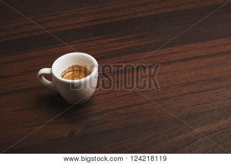 Side View Of Perfect Espresso In Small White Ceramic Cup On Red Wooden Table In Cafe Shop, Isolated