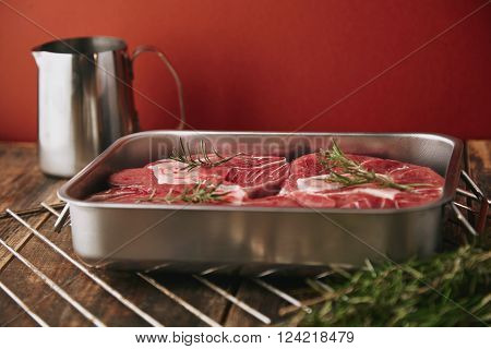 Three Pieces Of Fresh Raw Meat Steaks In Steel Stainer Ready To Cook, Isolated On Aged Vintage Woode