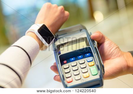 Woman using wearable smartwatch for paying on pos machine