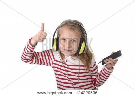 sweet little girl 7 years old with blonde hair and blue eyes listening to music with headphones and mobile phone giving thumb up enjoying song happy