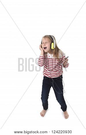 sweet little girl 7 years old with blonde hair and closed eyes listening to music with headphones and mobile phone singing and dancing happy and excited isolated on white background