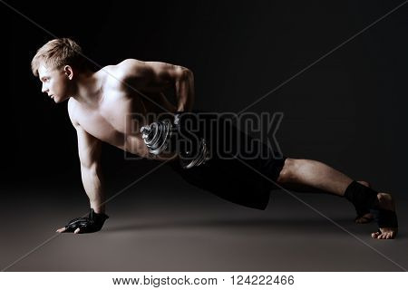 Handsome muscular male athlete performs gymnastic exercise. Sports, acrobatics, gymnastics.