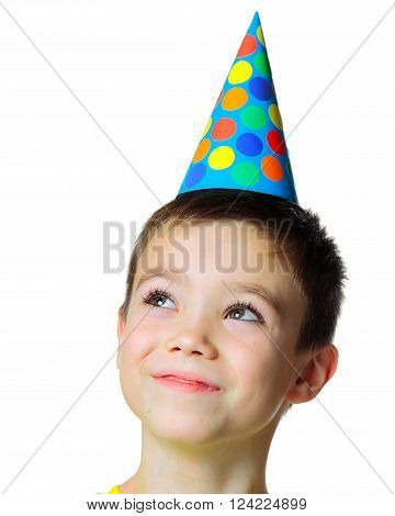 Portrait of eight years boy with birthday cap looking up on white background
