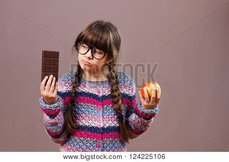 Cute little nerdy girl is holding apple and chocolate in her hands,she is sad because she must eat fruit,she would rather eat chocolate.