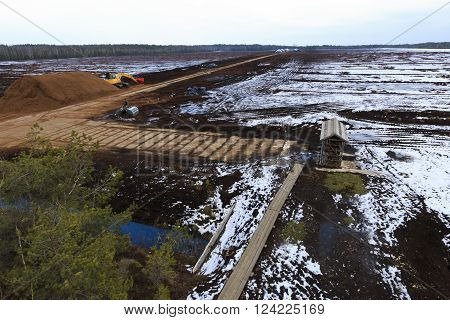 Peat extraction field in winter with tractor-type machinery.