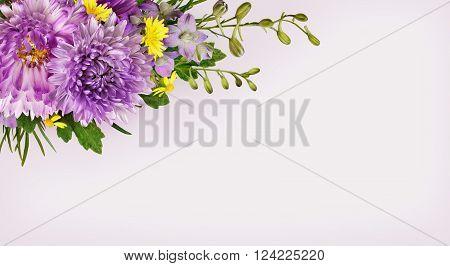 Purple and yellow flowers corner arrangement on gray background