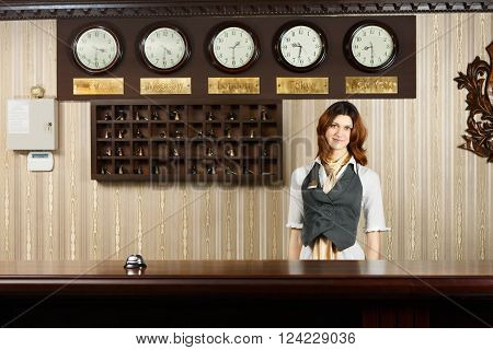 Hotel reception. Female receptionist at reception. Modern hotel reception counter desk with bell. Woman receptionist, concierge at desk. Travel, hospitality, hotel booking concept.