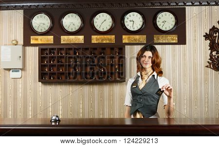 Hotel reception. Female receptionist at reception gives card to a guest. Modern hotel reception counter desk with bell. Woman receptionist at desk. Travel, hospitality, hotel booking concept.