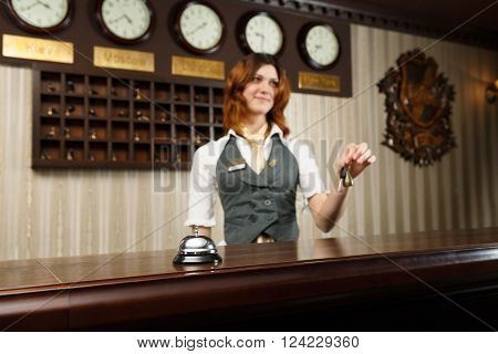 Modern hotel reception counter desk with bell. Hotel receptionist gives keys to a guest. Woman receptionist at desk unfocused. Selective focus at counter bell. Travel, hospitality concept.