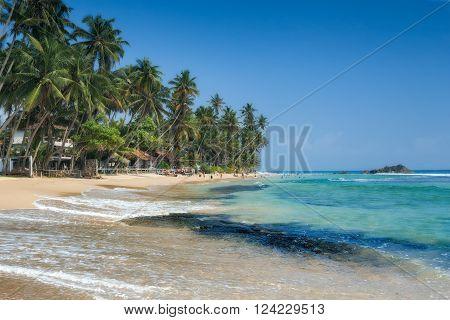 Unidentified people on the beach at Hikkaduwa. Hikkaduwa's beach and night life make it a popular tourist destination. Sri Lanka