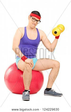 Vertical shot of a determined nerdy guy exercising with a dumbbell seated on an exercise ball isolated on white background
