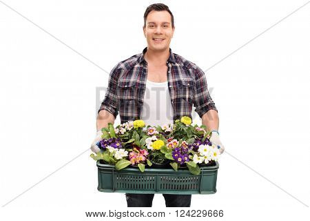 Young cheerful gardener holding a plastic crate full of beautiful flowers isolated on white background