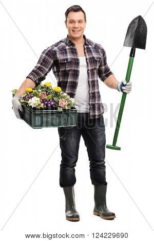 Full length portrait of a young gardener holding a shovel and a crate full of flowers isolated on white background