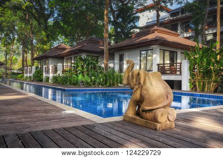 Thailand. Ko Chang. December 13, 2011: Elephant sculpture on a wooden floor by the pool, next to the white house surrounded by greenery.