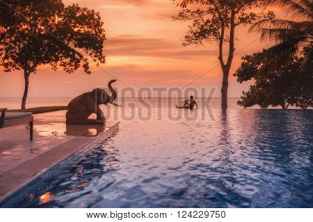 Thailand. Ko Chang. December 13, 2011: An unidentified man sitting on the edge of the pool. Elephant sculpture by the pool, overlooking the ocean in the evening, colorful, sunset light.