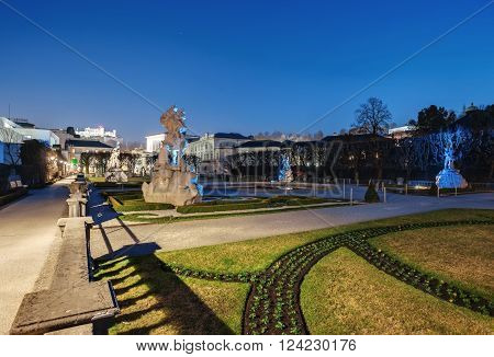 Beautiful view of famous Mirabell Gardens with the old historic Fortress Hohensalzburg in the evening in Salzburg, Austria