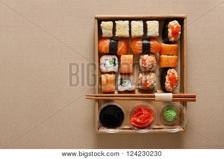 Japanese food restaurant, sushi rolls, gunkan plate or platter set. Copyspace. Chopsticks, ginger, soy sauce and wasabi. Sushi at carton, paperboard background in take away, delivery box. Top view.