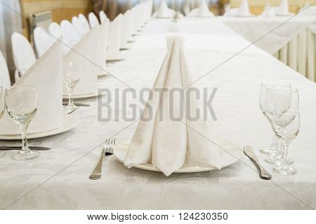 Beautifully organized event, glasses, napkin at served festive white table ready.  Event in restaurant. Banquet, wedding decor, celebration. Catering and event. Wedding tables. Large restaurant hall.