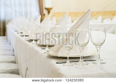 Beautifully organized event, glasses at served festive white table ready.  Event in restaurant. Banquet, wedding decor, celebration. Catering and event. Wedding tables. Large restaurant hall.