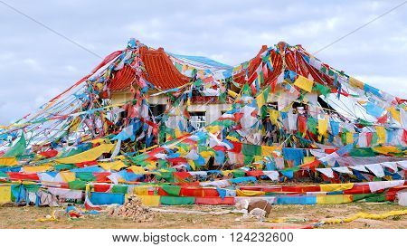 It is taken on the hill next to Nam Co, means heavenly lake. The abandoned houses is covered by colorful prayer flags.