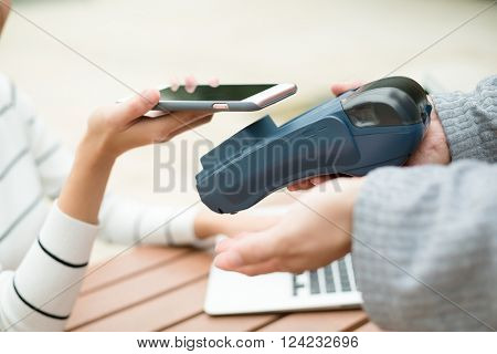 Woman pay the bill with cellphone