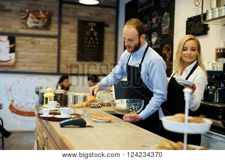 Waiter and waitress working in cafeteria behind counter.