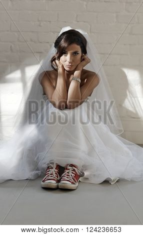 Serious bride sitting on floor wearing wedding gown and red sneakers.