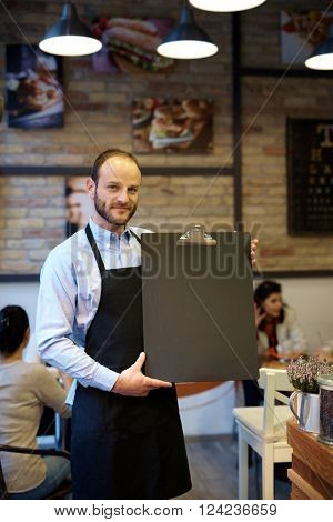 Waiter holding blank blackboard in hand, looking at camera.