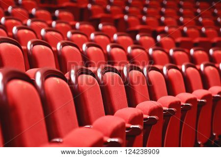 Rows of empty red velvet seats inside a theater