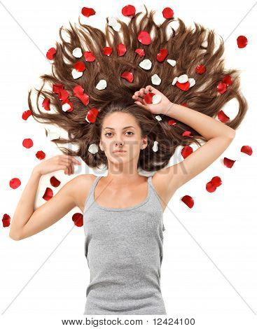 Young Beautiful Brunette Woman With Scattered Long Hairs And Rose Petals