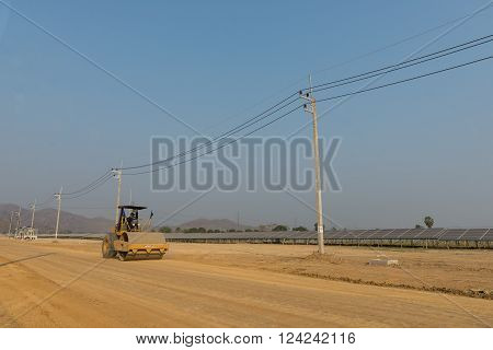 Petchaburi, Thailand - February 20, 2016: One worker drives soil compactor in the under construction solar farm on February 20, 2016 in Petchaburi, Thailand