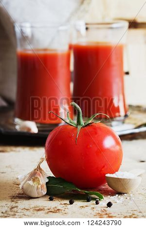 Ripe tasty tomatoes and glass of tomato juice on the old wooden background. Rustic style. Healthy food and drink concept. Selective focus