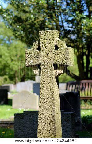 Celtic Cross in a cemetery, summer scene