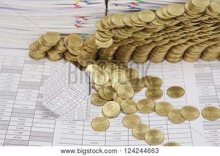 Close up bankruptcy of house on finance account have step pile of gold coins collapse and pile of paperwork as background.