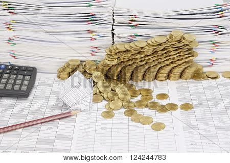 Pencil and bankruptcy of house on finance account have step pile of gold coins collapse with calculator and pile of paperwork as background.