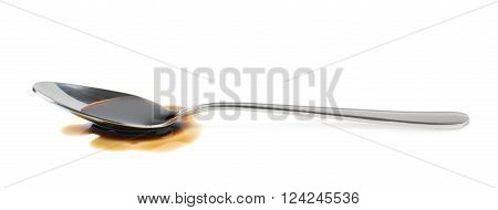 Steel spoon in a puddle of soy sauce isolated over the white background