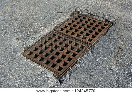 rustic square manhole drain cover in the street