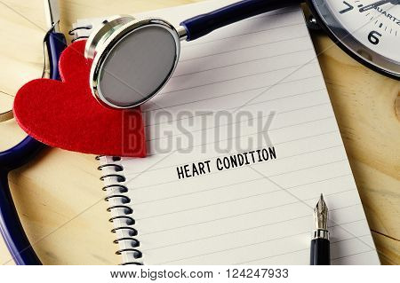 Medical Concept. Stethoscope, Heart Shape, Notepad, Clock And Pen On Wooden Table With Heart Conditi