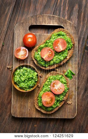 Bread with pesto sauce and tomatoes top view