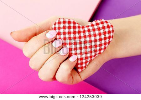 Female Hand With Manicure Holding Heart On A Colorful Background