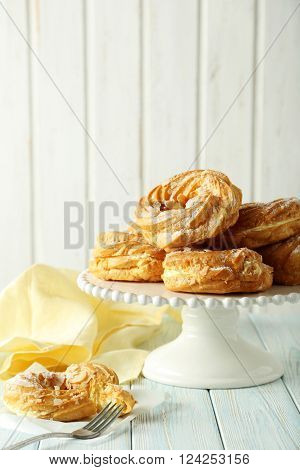Sweet Eclairs On A White Wooden Table