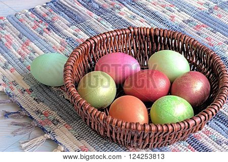 Easter eggs in a wicker basket on a homespun rug.