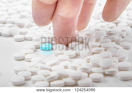 Man's hand choosing a blue tablet among white tablets. Concept is that only on drug among many others can help for a certain disease.