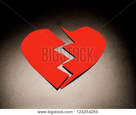 Red heart broken in two halves symbolizing relationship break up or depression.
