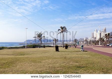 DURBAN SOUTH AFRICA - APRIL 1 2016: Many unknown people on early morning beach front against city skyline in Durban South Africa