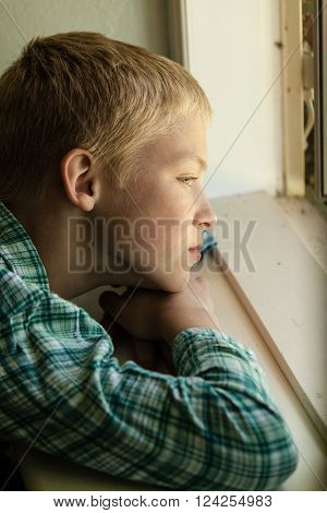 Child With Sad Expression Sitting Near Window