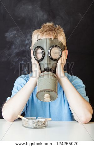 Miserable child with hands on face covered by chemical gas mask near glass tray of cigarettes on table